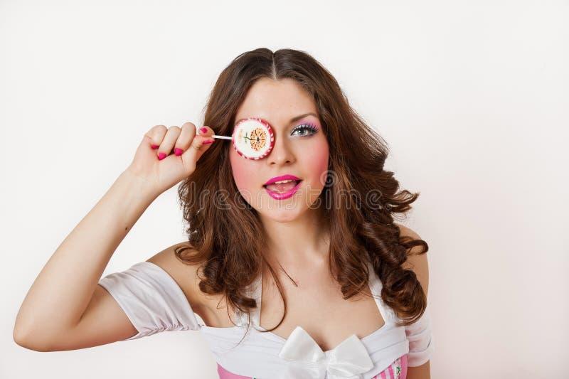 Aantrekkelijk meisje met een lolly in haar hand en roze die kleding op wit wordt geïsoleerd. Het mooie lange haar donkerbruine spe royalty-vrije stock afbeeldingen