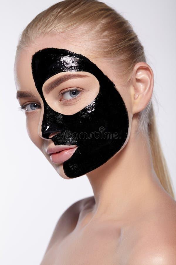 Aantrekkelijk meisje met een zwart masker op het gezicht stock afbeelding