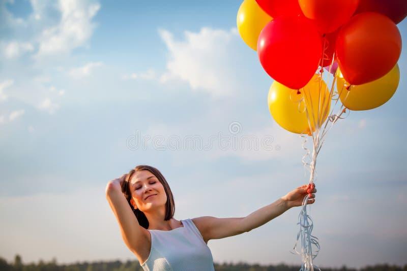 Aantrekkelijk meisje met luchtballons op blauwe hemelachtergrond gelukkig stock afbeeldingen