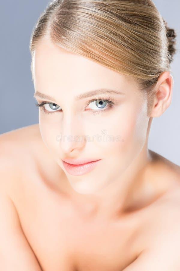 Aantrekkelijk meisje met vlotte huid over de grijze achtergrond royalty-vrije stock afbeeldingen