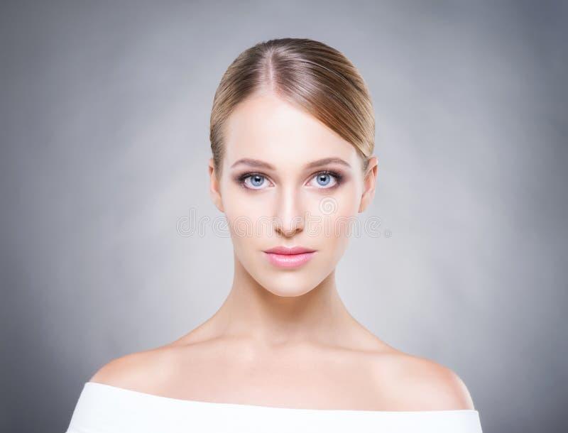 Aantrekkelijk meisje met vlotte huid over de grijze achtergrond stock fotografie