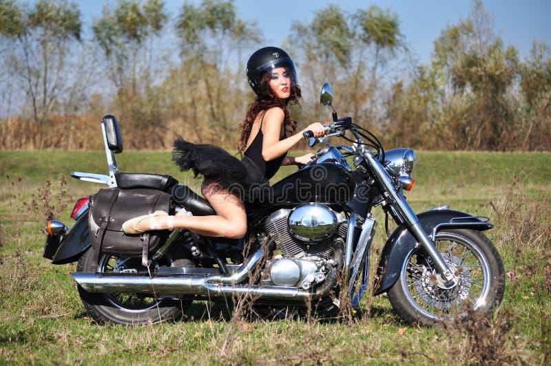 Aantrekkelijk meisje op een motor die buiten stellen royalty-vrije stock foto