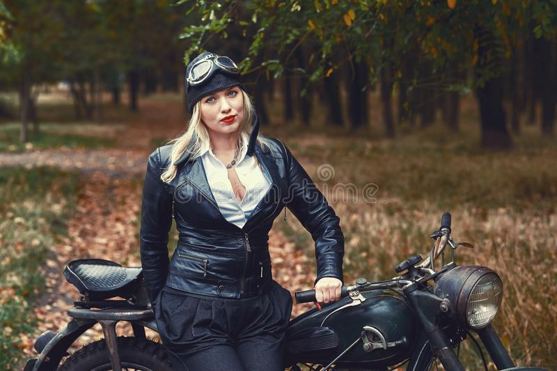 Aantrekkelijk meisje op een oude motorfiets in het de herfstpark stock afbeeldingen