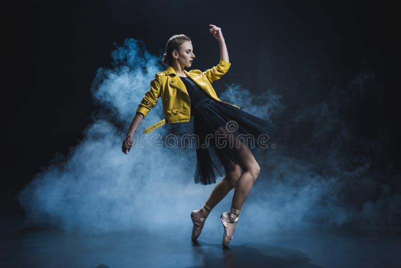 aantrekkelijk meisje in pointeschoenen en zwarte tutu dansen en geel leerjasje die in studio royalty-vrije stock afbeelding