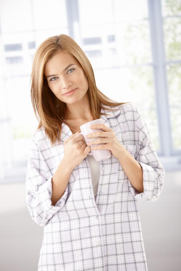 Aantrekkelijk meisje in pyjama het drinken thee het glimlachen stock afbeelding