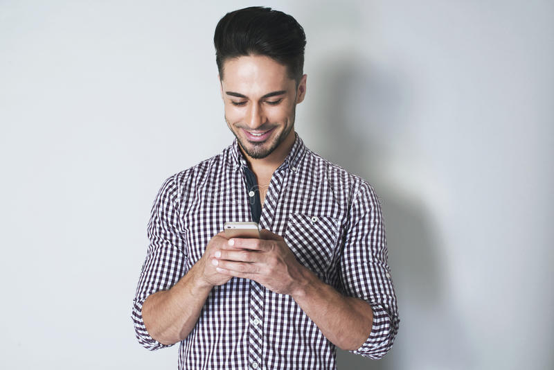 Aantrekkelijk mens het typen bericht bij zijn mobiele telefoon royalty-vrije stock afbeelding
