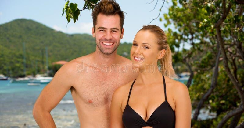 Aantrekkelijk millennial paar die zich bij het strand bevinden die terwijl op cruise glimlachen stock afbeeldingen