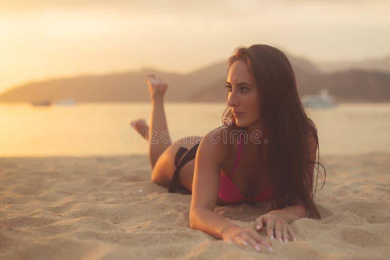 Aantrekkelijk model met bruin haar dat bikini draagt die de zomer van vakantie geniet die op zandig strand bij zonsondergangoverz stock fotografie