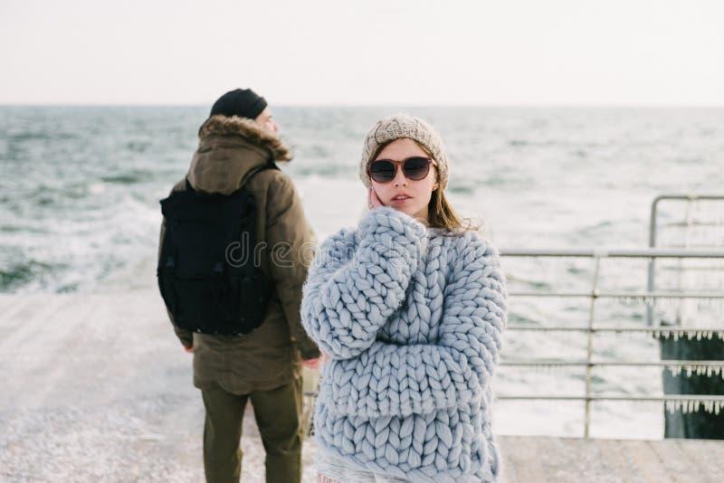 aantrekkelijk modieus meisje in zonnebril en merinoswolsweater op de vriend van de de winterkade royalty-vrije stock afbeelding
