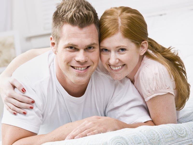 Aantrekkelijk paar dat op hun bed koestert stock afbeeldingen