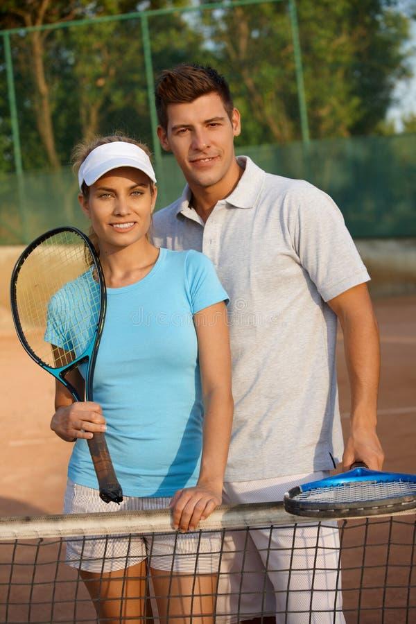 Aantrekkelijk paar dat op tennisbaan glimlacht royalty-vrije stock foto's
