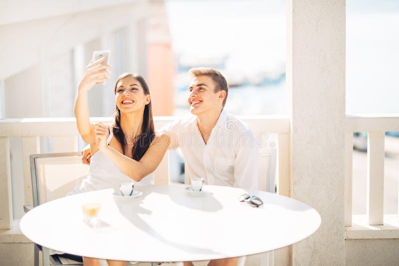 Aantrekkelijk paar die eerste datum hebben Koffie met een vriend Glimlachende gelukkige mensen die een selfie met een smartphone  royalty-vrije stock foto