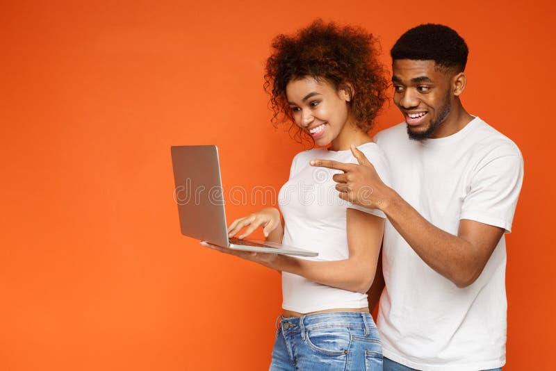 Aantrekkelijk paar die hun reis met laptop plannen stock fotografie