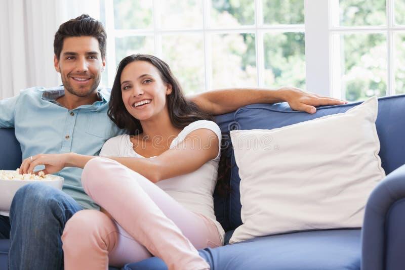 Aantrekkelijk paar die op TV op de laag letten royalty-vrije stock foto's