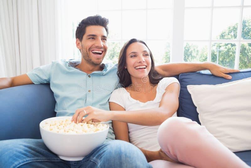 Aantrekkelijk paar die op TV op de laag letten stock foto's