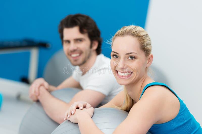 Aantrekkelijk paar die pilates oefeningen in een gymnastiek doen stock foto