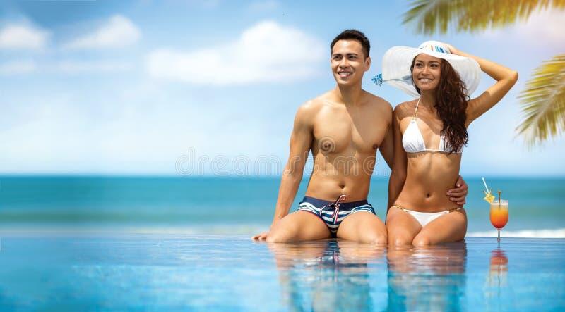 Aantrekkelijk paar die terwijl het zitten door een zwembad zonnebaden stock foto's