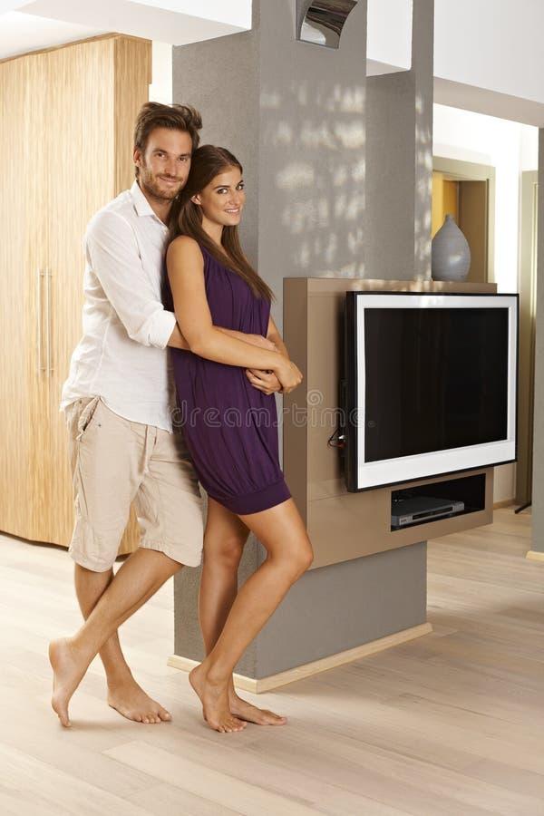 Aantrekkelijk paar die thuis omhelzen stock foto