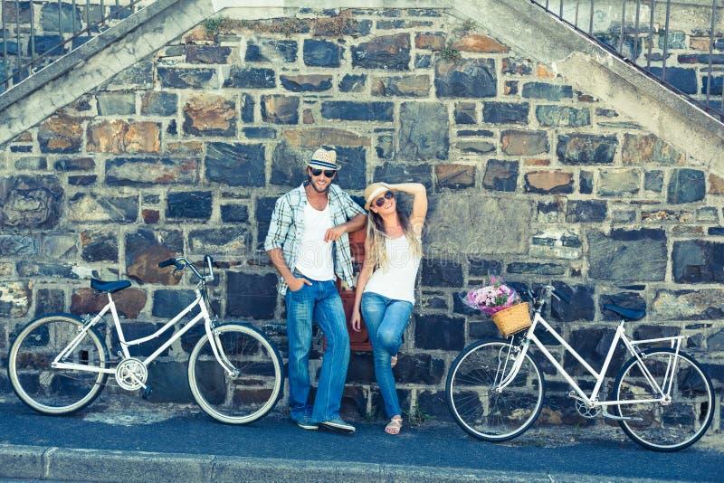 Aantrekkelijk paar die zich met fietsen bevinden stock foto's