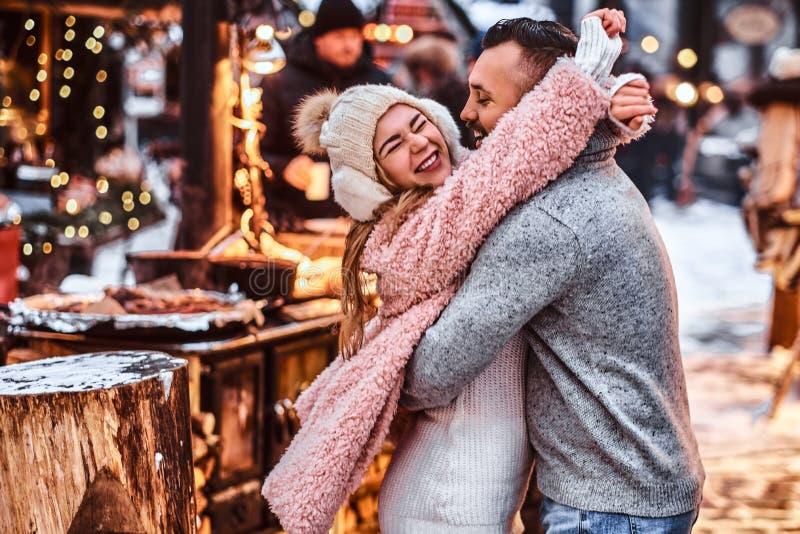 Aantrekkelijk paar in liefde, die samen doorbrengend tijd terwijl het omhelzen bij de de wintermarkt in een Kerstmistijd genieten stock foto's