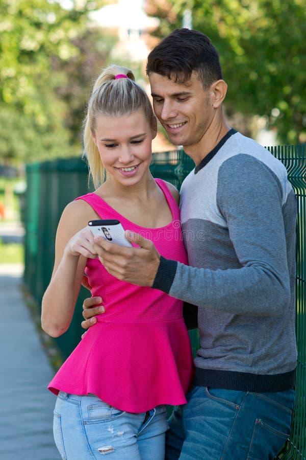 Aantrekkelijk paar met buiten smartphone stock foto's