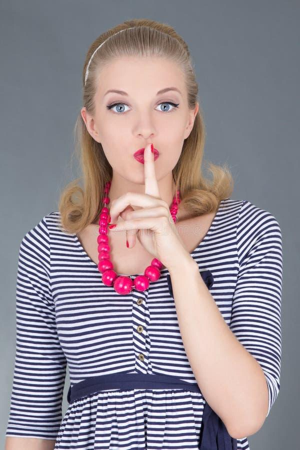 Aantrekkelijk pinupmeisje in gestreepte kleding met vinger op lippen royalty-vrije stock afbeelding