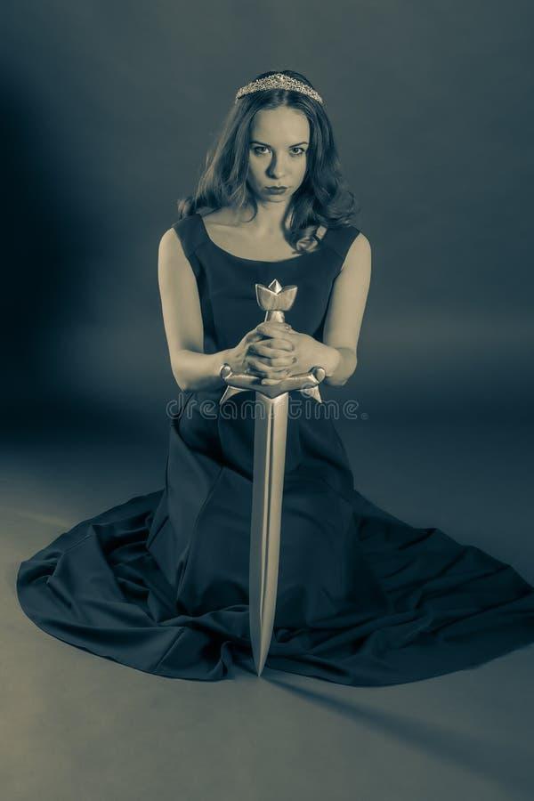 Aantrekkelijk prinsesmeisje die met een zwaard knielen royalty-vrije stock fotografie