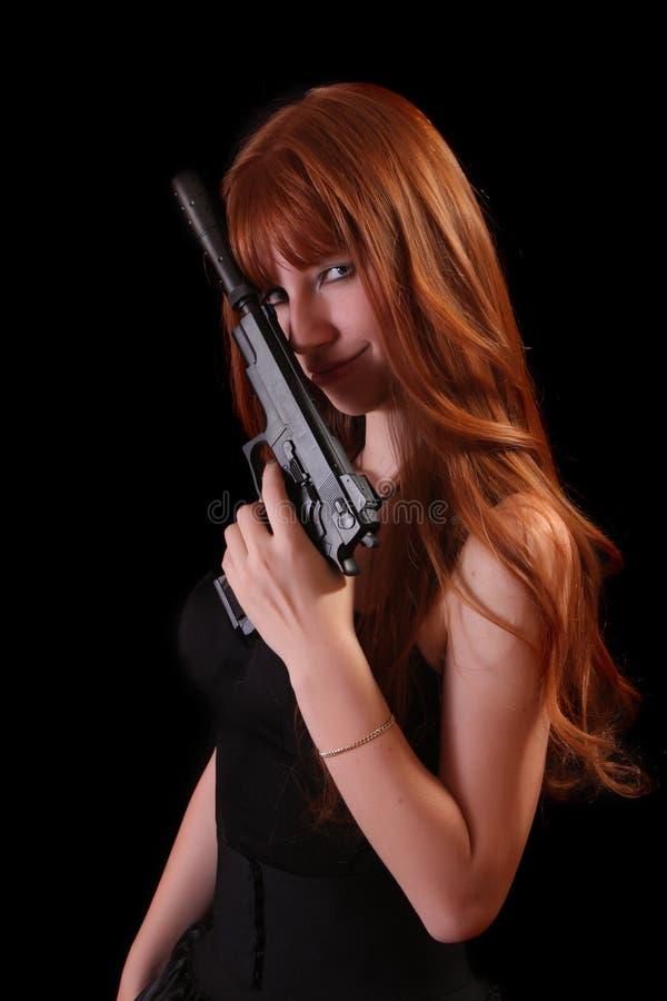 Aantrekkelijk rood meisje met kanon op zwarte royalty-vrije stock foto