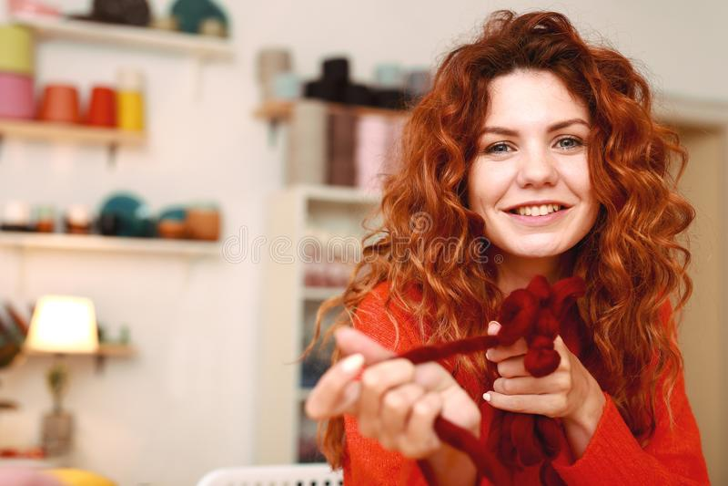 Aantrekkelijk roodharig meisje die kastanjebruine sweater breien stock fotografie