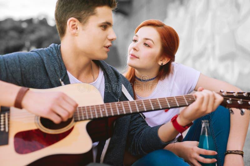 Aantrekkelijk roodharig tienermeisje die haar knappe vriend met gitaar bekijken royalty-vrije stock fotografie