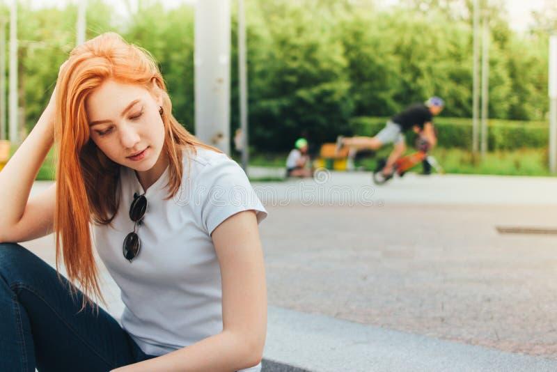 Aantrekkelijk roodharige glimlachend meisje die in vrijetijdskleding op straat in stad, actieve mensen op achtergrond zitten royalty-vrije stock foto
