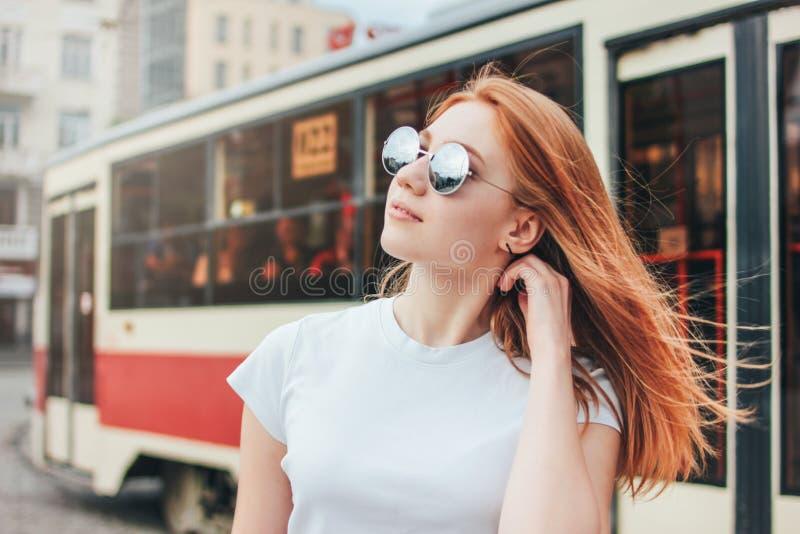 Aantrekkelijk roodharige glimlachend meisje in zonnebril in vrijetijdskleding op tramachtergrond bij straat in stad stock afbeeldingen