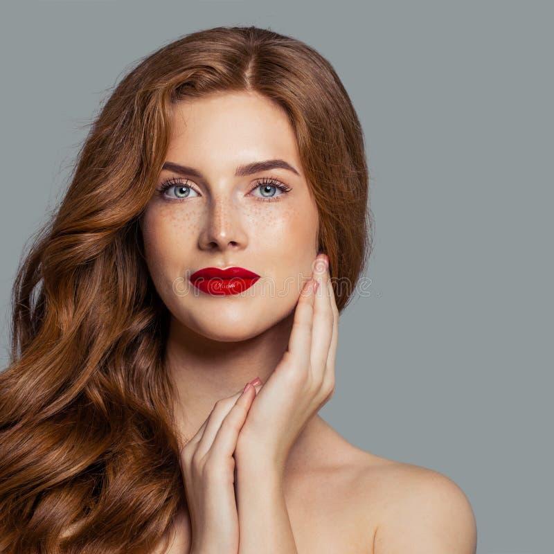 Aantrekkelijk roodharigemeisje dat met rode lippenmake-up camera bekijkt stock foto's