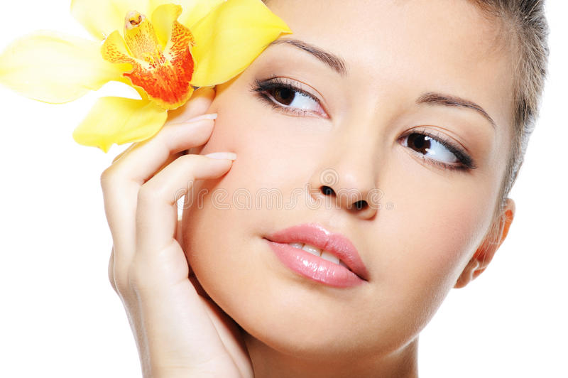 Aantrekkelijk schoonheids Aziatisch vrouwelijk gezicht met bloem stock foto's