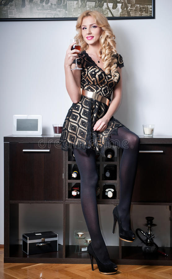 Aantrekkelijk sexy blondewijfje die zwarte kleding dragen  stock afbeelding