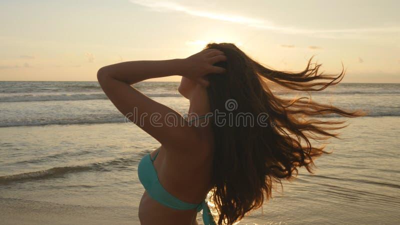 Aantrekkelijk sexy meisje met het lange haar stellen op de oceaankust bij zonsopgang Mooie jonge vrouw in bikini die zich dichtbi stock afbeeldingen