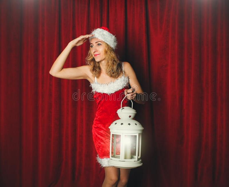 Aantrekkelijk sneeuwmeisje in een rode kleding en hoed met wit flitslicht in haar hand op een achtergrond van rode gordijnen r royalty-vrije stock fotografie