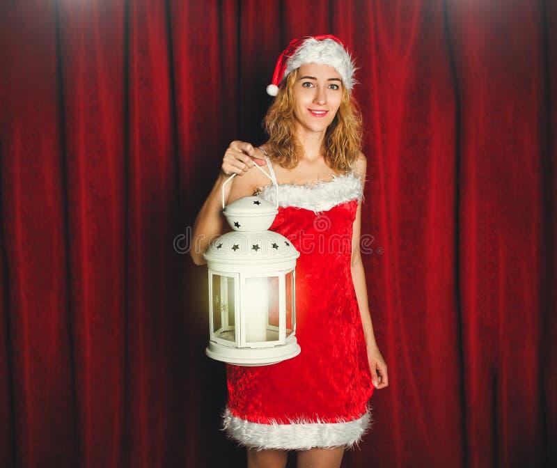 Aantrekkelijk sneeuwmeisje in een rode kleding en hoed met wit flitslicht in haar hand op een achtergrond van rode gordijnen r royalty-vrije stock afbeelding