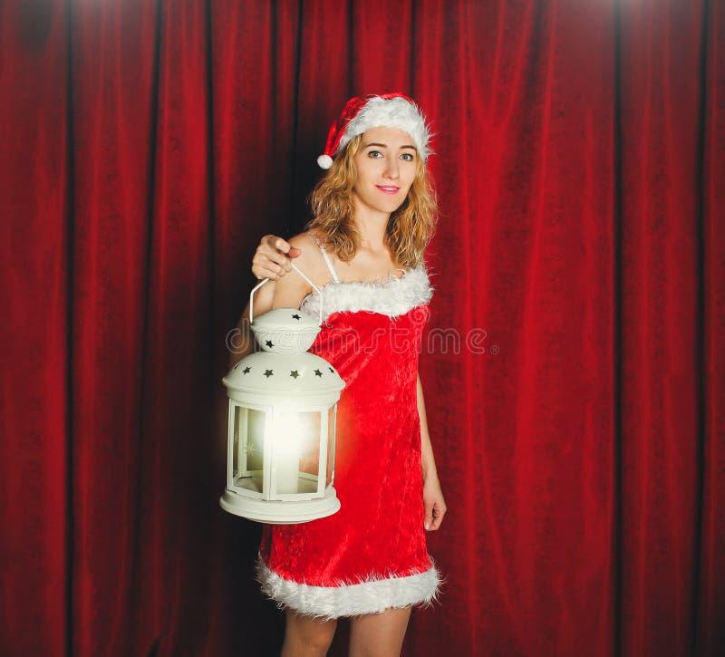 Aantrekkelijk sneeuwmeisje in een rode kleding en hoed met wit flitslicht in haar hand op een achtergrond van rode gordijnen r royalty-vrije stock foto's