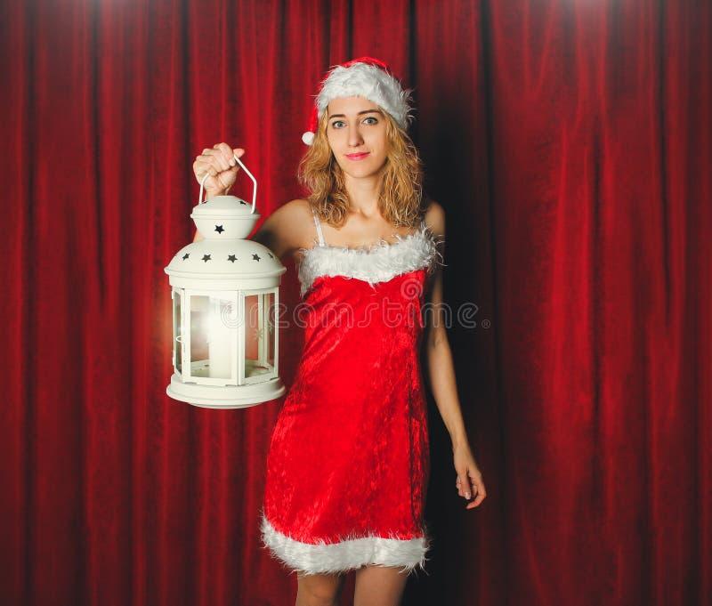 Aantrekkelijk sneeuwmeisje in een rode kleding en hoed met wit flitslicht in haar hand op een achtergrond van rode gordijnen r stock foto