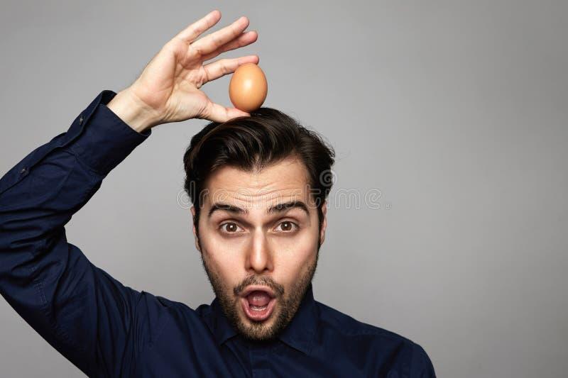 Aantrekkelijk Spaans de kippen vers organisch ei van de mensenholding over van hoofd op grijze achtergrond Sluit omhoog royalty-vrije stock foto's