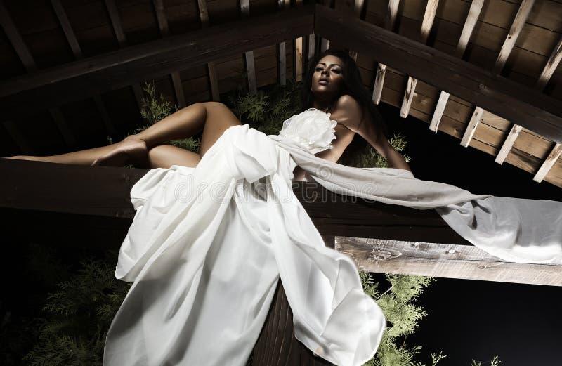 Aantrekkelijk suntanned meisje in witte kleding stelt. stock foto