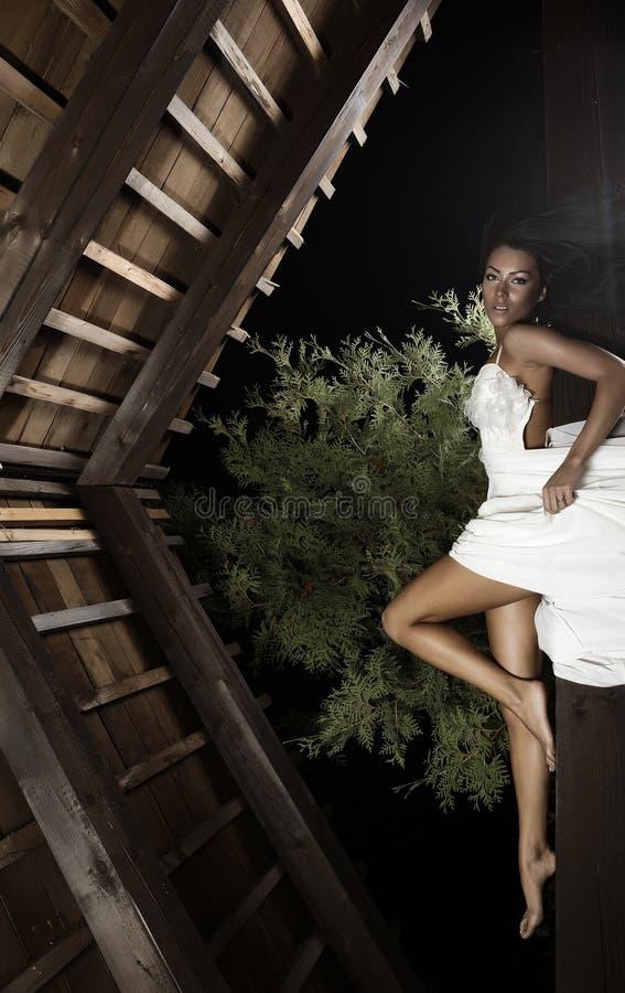 Aantrekkelijk suntanned meisje in witte kleding stelt. stock afbeelding