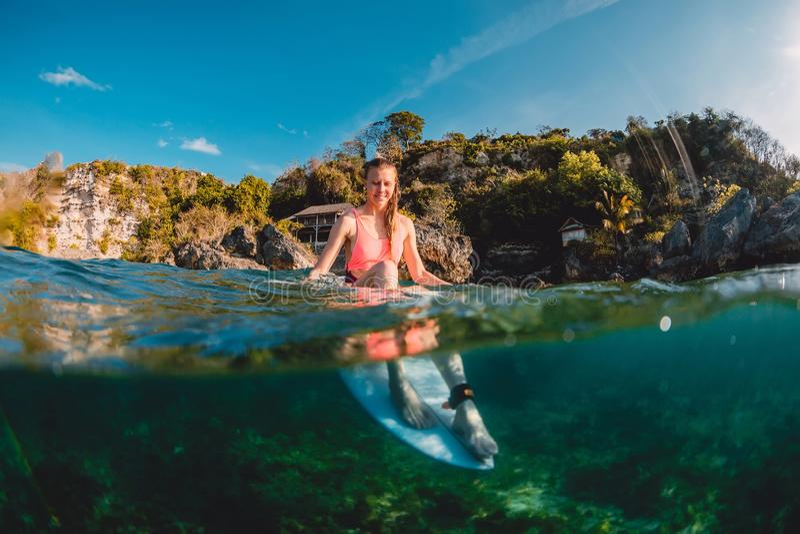Aantrekkelijk surfermeisje met surfplank De surfer zit bij raad stock afbeelding