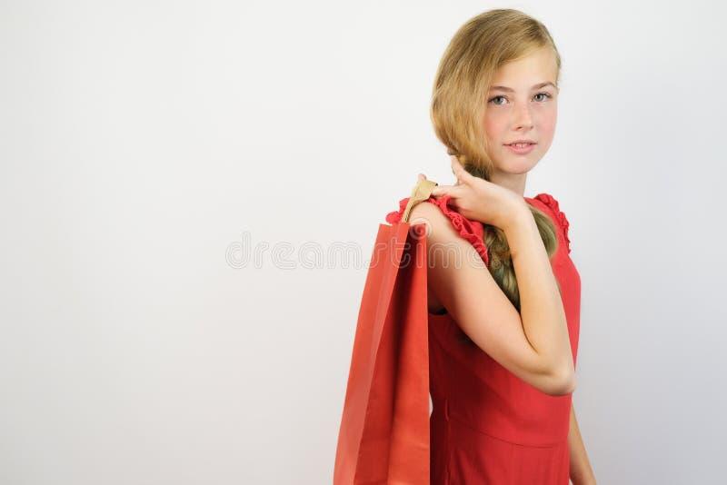 Aantrekkelijk tiener Kaukasisch meisje die een document pakket met aankopen in haar hand houden stock afbeelding