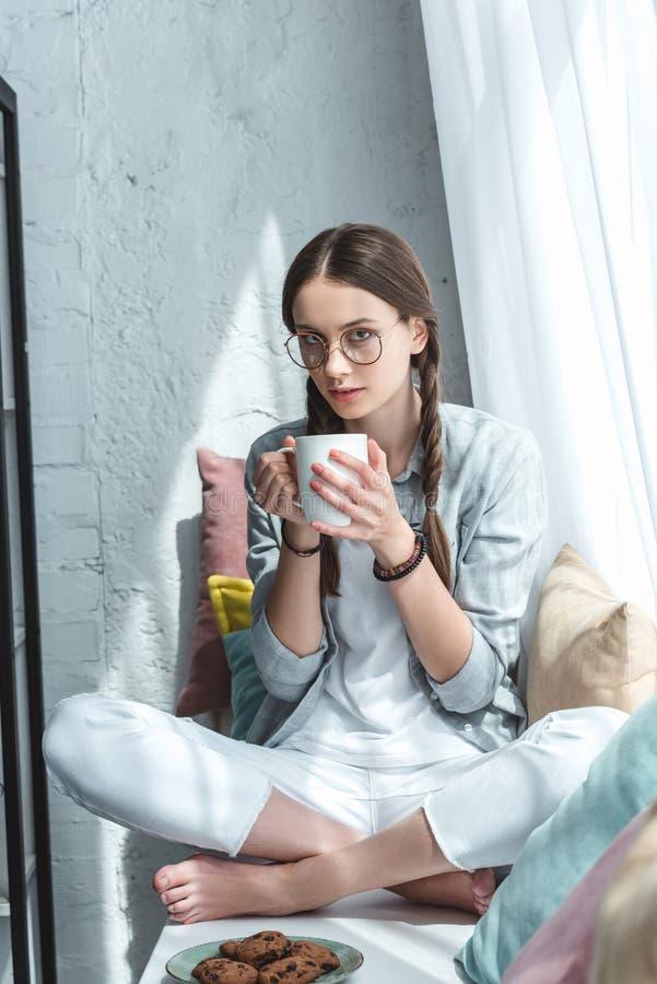 aantrekkelijk tienermeisje die koekjes met koffie op vensterbank eten royalty-vrije stock foto