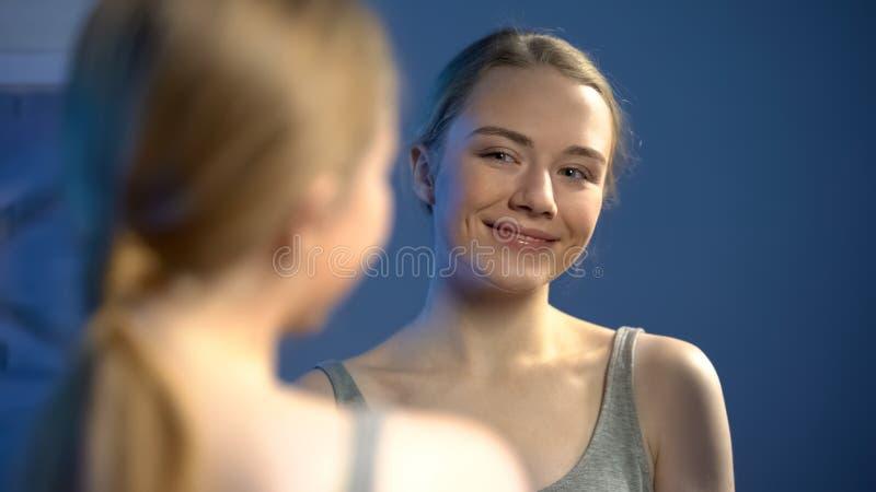 Aantrekkelijk tienermeisje die spiegel tevreden met bezinning, jonge schoonheid bekijken stock afbeeldingen