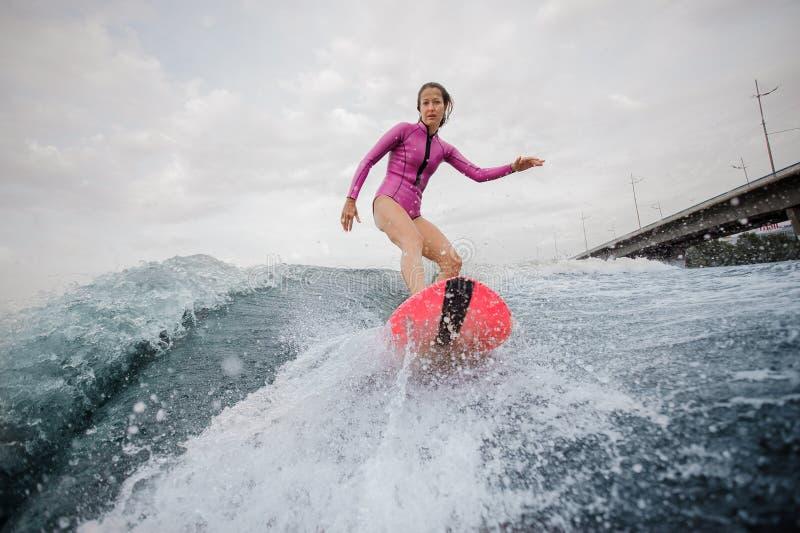 Aantrekkelijk tienermeisje in roze zwempak die op oranje w berijden stock fotografie