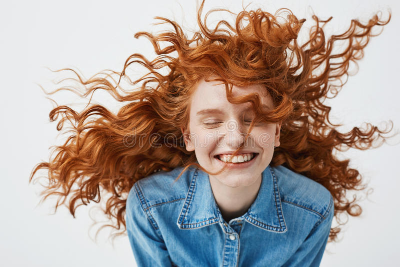Aantrekkelijk vrolijk roodharigemeisje met het vliegen het krullende haar glimlachen die met gesloten ogen over witte achtergrond royalty-vrije stock foto's