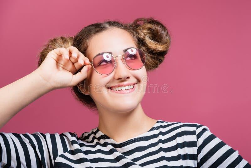 Aantrekkelijk vrolijk tienermeisje die zonnebril over roze achtergrond dragen stock afbeeldingen